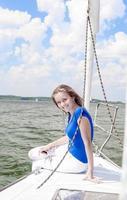 lächelnde positive kaukasische Frau, die auf weißer Yacht entspannt