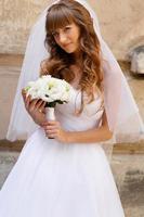 stilvolle junge schöne kaukasische blonde Braut, die gegen th aufwirft foto