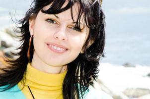 junge freudig lächelnde kaukasische Brünette am hellen sonnigen Strand