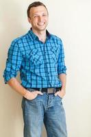 junger positiver kaukasischer Mann im Freizeithemd, Studioporträt foto