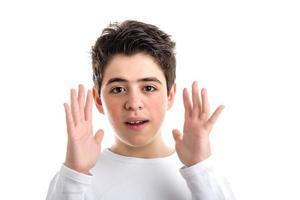kaukasischer Junge mit glatter Haut, der offene Hände entlang des Gesichts winkt foto