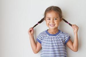 Porträt des glücklichen, positiven, lächelnden, verspielten asiatischen kaukasischen Kindes foto