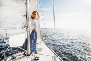 junge kaukasische Frau auf einem Segelboot, das am Horizont starrt foto