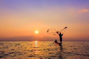 Fischernetz während des Sonnenuntergangs werfen, thailändisch foto