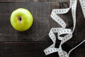 ein Apfel, umgeben von einem Maßbandschneider auf Holz foto