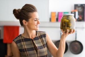 Frau hält großes Glas mit frisch zubereiteten Dillgurken hoch foto