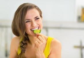 Porträt der jungen Frau, die Gurke in der Küche isst foto