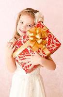 Porträt des glücklichen entzückenden kleinen Mädchens mit Geschenkbox