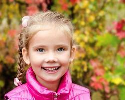 Herbstporträt des niedlichen lächelnden kleinen Mädchens foto