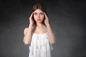 Mädchen zeigt, dass sie Kopfschmerzen hatte foto