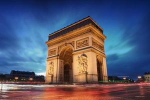 Arc de Triomphe in Paris bei Sonnenuntergang mit verschwommenen Autos foto