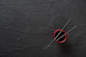 Essstäbchen und Schüssel mit Sojasauce auf schwarzem Steinhintergrund foto