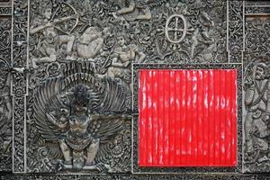 alter balinesischer Steinschnitzhintergrund mit dem roten quadratischen Schild