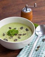 hausgemachte grüne Brokkoli-Cremesuppe in weißer Schüssel serviert foto
