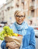 junge hübsche blonde Frau mit Essen in der Tasche, die weitergeht foto