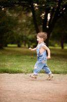 glücklicher kleiner Junge, der in einem Park läuft foto