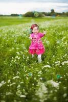 schönes sorgloses Mädchen, das draußen im Feld spielt foto