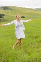 sorglose Arme der jungen Frau öffnen sich im Grasland