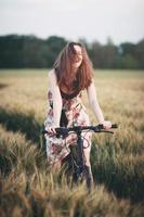 glückliche junge Frau, die ein Fahrrad in einem Weizenfeld reitet foto