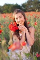 junge Frau, die Strauß roter Mohnblumen kuschelt und Natur genießt foto