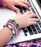 junges Mädchen mit Webstuhlarmbändern auf Laptop foto