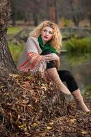 blondes Mädchen trägt grüne Bluse und großen Schal, der draußen aufwirft foto