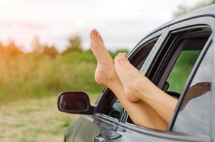 Frauenbeine aus dem Autofenster.