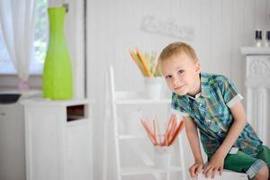 Porträt des glücklichen blonden Jungenkindes, das auf Stuhl sitzt foto