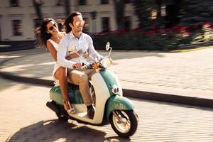 fröhliches junges Paar, das einen Roller fährt