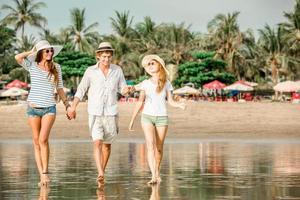 Gruppe glücklicher junger Leute, die am Strand entlang gehen foto
