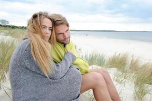 attraktive schöne Frau und Mann sitzen am Strand foto