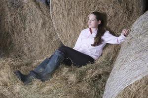 nachdenkliche Frau, die sich in der Scheune entspannt foto