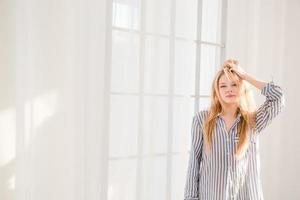sorglose junge Frau mit zerzausten Haaren, die nahe Fenster stehen foto