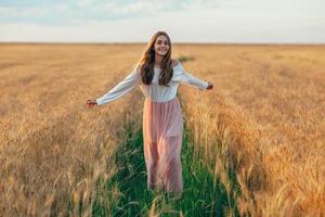 schöne brünette Dame im Weizenfeld bei Sonnenuntergang