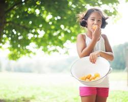 Mädchen hält Schüssel und isst Aprikose foto