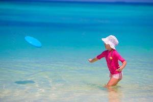 kleines Mädchen, das mit fliegender Scheibe am weißen Strand spielt foto