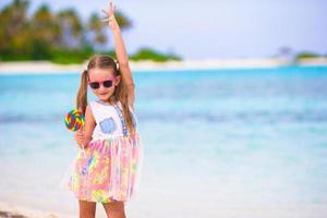 entzückendes kleines Mädchen viel Spaß mit Lutscher am Strand