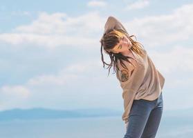 junge asiatische Frau, die über Hintergrund des blauen Himmels tanzt.
