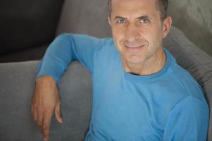 heiterer glücklicher Mann, der auf Sofa zu Hause entspannt foto