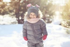 glückliches lächelndes Kind, das im sonnigen Wintertag geht foto