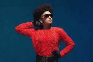 Frau posiert in modischer Kleidung mit Sonnenbrille