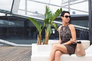 erfolgreiche junge Geschäftsfrau in Sonnenbrille, die an modernem Platz ruht