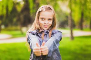 junges Mädchen legt ihre großen Daumen hoch foto