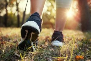 Frauenfüße zu Beginn des Rennens. Konzept, Sonnenuntergang foto