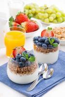 leckeres Dessert mit Sahne, frischen Beeren und Müsli, vertikal foto