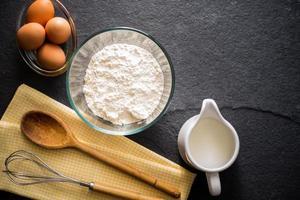 Backzutaten - Mehl, Milch, Eier mit einem Schneebesen foto