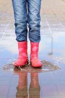 das Mädchen in rosa Stiefeln springt in Pfützen