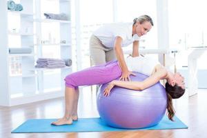 Trainer hilft Frau auf Gymnastikball foto