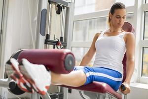 hübsche junge Frau, die im Fitnessstudio trainiert foto