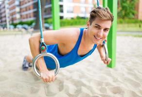junger Mann, der im Fitnessstudio im Freien trainiert foto